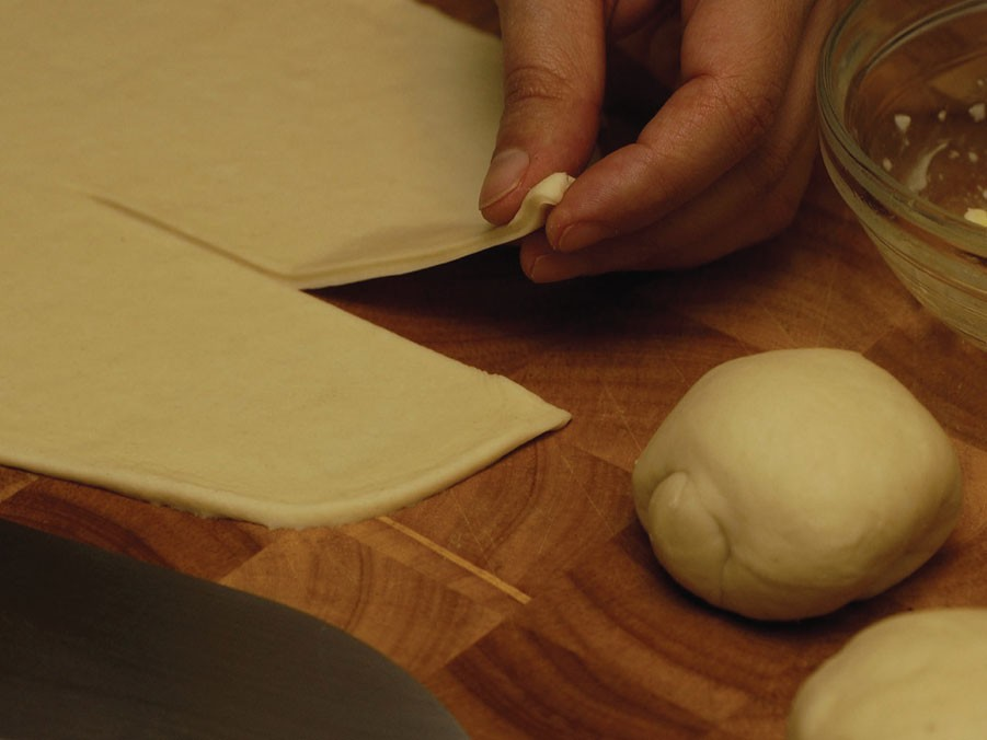 Roll out the dough in to a circle and cut halfway down the middle.