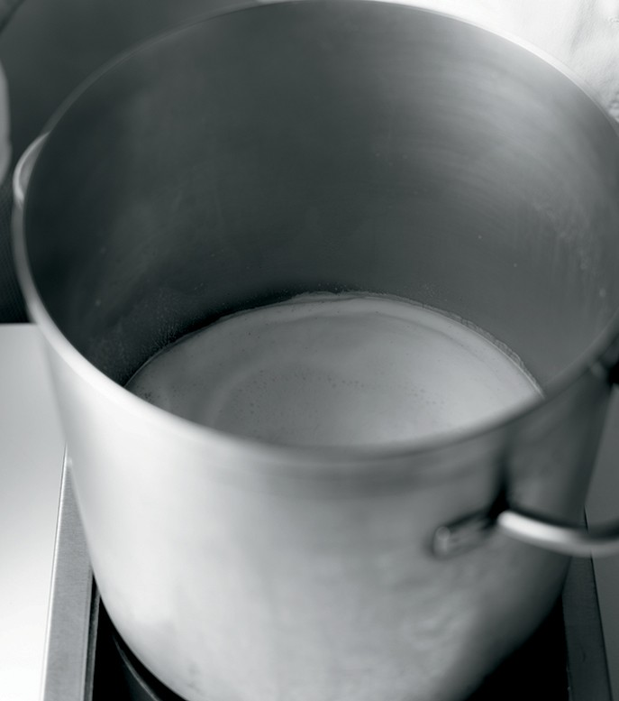 Warm the first amount of milk along with the sugar and any flavorings in a large deep pot. Bring the mixture to a rolling boil.
